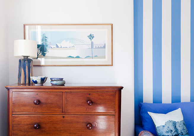 Chest of Drawers with blue and white striped wall and blue sofa by 2 Lovely Gays