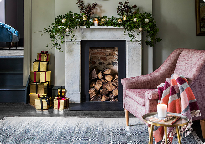 Joan Armchair in pink by Perch & Parrow next to open fireplace with Christmas decoration and presents