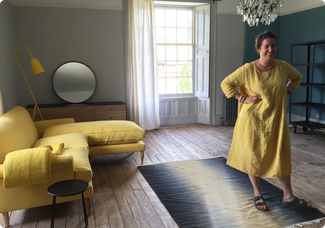 Astrid on set in yellow dress alongside yellow Peter 3-Seater Chaise in yellow