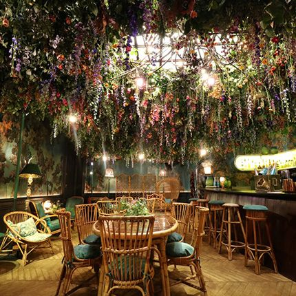 Glade Room at Sketch London with wicker furniture and floral ceiling display