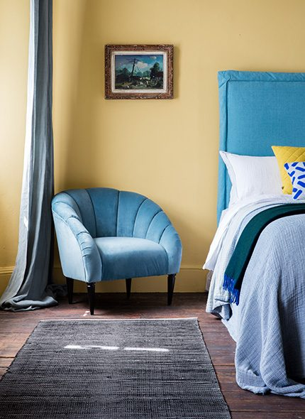 Blue Tilly Headboard in guestroom interior with Joan Armchair by Perch and Parrow