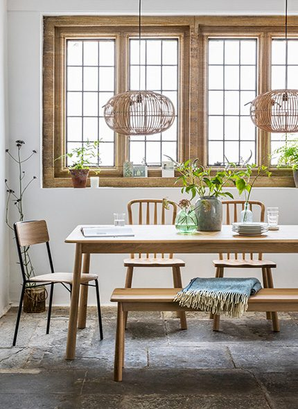 Wooden dinning table and chairs, surround by green plants and wicker hanging pendant lights
