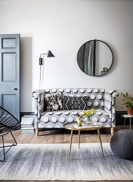 Living room with a spotty grey, white and black fabric Simon 2-seater sofa. Grey and white rug, circle black mirror and black wall light.