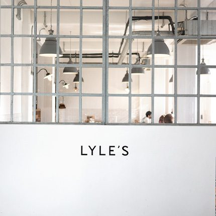 Lyle's restaurant sign on white wall with pendant lights in background
