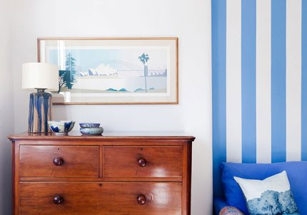 Blue striped wall with wooden chest of drawers from the 2 lovely gays