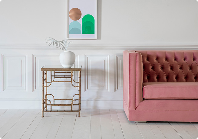 Gold wired side table with pink James sofa in an art deco style living room