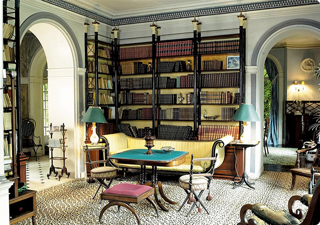 Madeleine Castaing blue interior library with gold bookcase and blue and green top tables