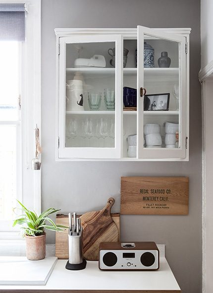 white cabinet and wall image of a kitchen counter with wooden ornaments and pot plant.