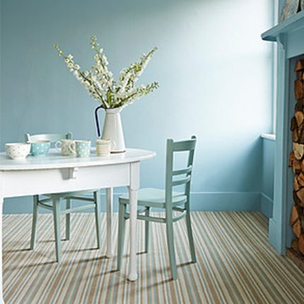 light blue coloured wall dining room in Lucy Goughs house with painted white wood table and painting blue chairs