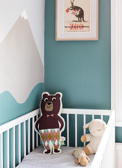 : Lucy Goughs mountain wall painted childrens bedroom with white cot.