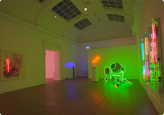 gallery interior shot of coloured neon light sculptures in pink, green and blue.