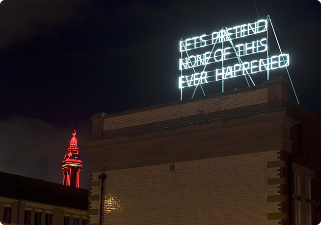 building exterior with white light neon sign reading 'let's pretend this never happened'
