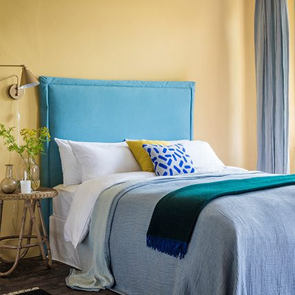 Blue fabric covered made to order Tilly Headboard in yellow walled bedroom interior and teal Herbie throw Perch & Parrow