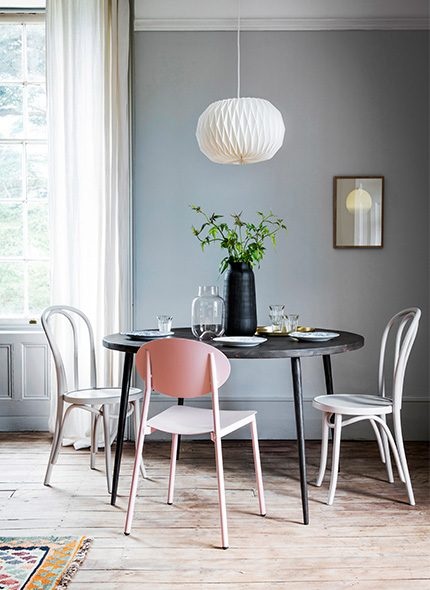 Diningroom interior with black circular table and pink and black wood painted chairs with a white paper lampshade pendant light