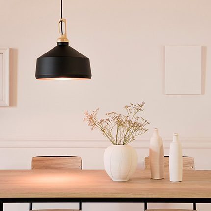 black and brass pendant hanging light in a dining room interior with pink walls