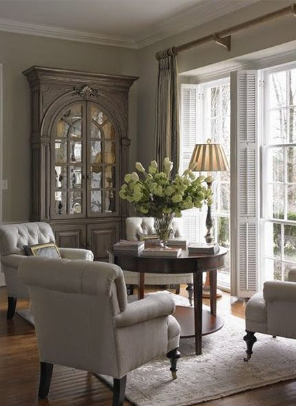 White walled French country living room interior with white fabric coated armchair and wooden furniture