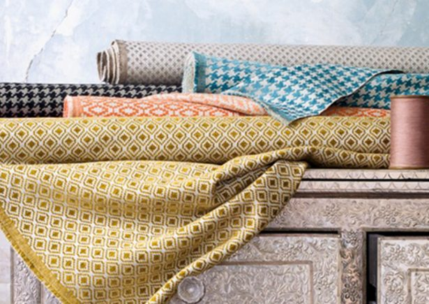 rolled fabrics in yellow and blue patterns on a chest of drawers