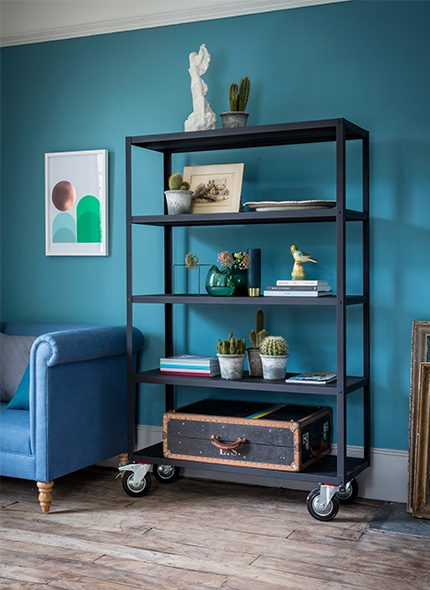 Simon 2 Seater Sofa in blue fabric with black shelving unit on wheels in a livingroom interior Made to order by Perch & Parrow