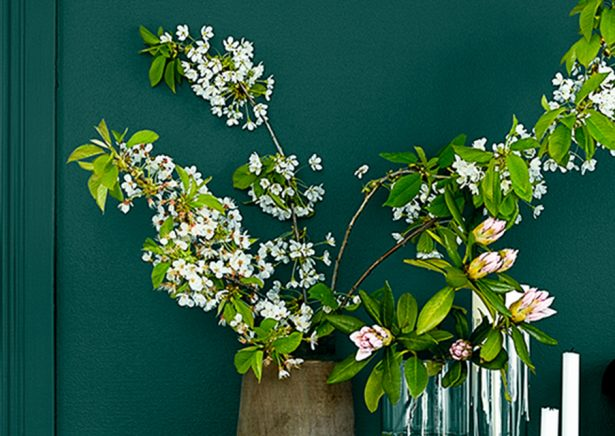 Green painted wall background with floral vases