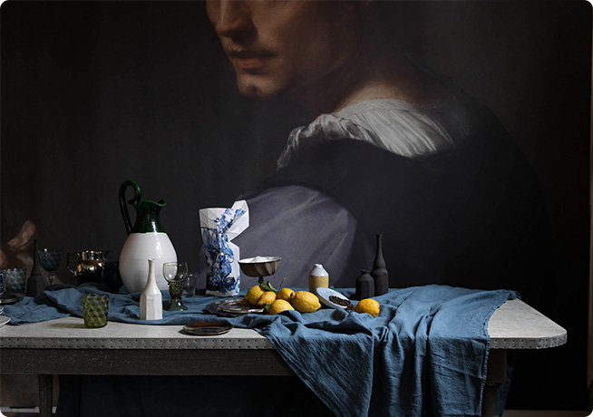 Ali Brown homepage art direction of dark dining table set and portrait painted wall
