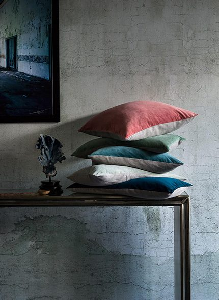 grey walled interior image of piled pillows in red, green and blue on top of a console by Ali Brown