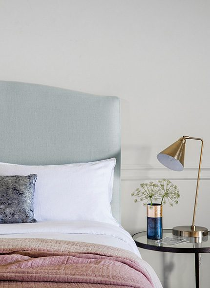 Light blue upholstered Astro Headboard in a bedroom interior with side table and lamp by Perch & Parrow