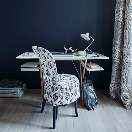 dark blue walled study interior with patterned chair covering and desk by Ali Brown